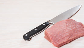 Food background of knife and raw meat at the wooden board Royalty Free Stock Photo