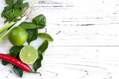 Food Background with Limes Coriander, Red Chilli and Spring Onio. Kaffir lime leaves, fruit, coriander or cilantro, red chilli and green onions over white Royalty Free Stock Photography
