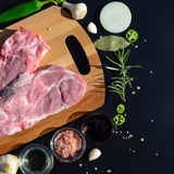 Food background. Meat on a cutting board and pepper, bay leaf, rosemary, onions, Himalayan salt, olive oil, soy sauce on a black b Royalty Free Stock Photos