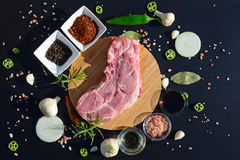 Food background. Meat on a cutting board and pepper, bay leaf, rosemary, onions, Himalayan salt, olive oil, soy sauce on a black b Royalty Free Stock Photography