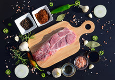 Food background. Meat on a cutting board and pepper, bay leaf, rosemary, onions, Himalayan salt, olive oil, soy sauce on a black b Royalty Free Stock Image