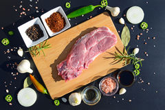 Food background. Meat on a cutting board and pepper, bay leaf, rosemary, onions, Himalayan salt, olive oil, soy sauce on a black b Stock Photo