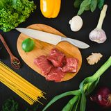 Food background with meat on wooden board, knife, pasta and vegetables on dark table. Top view. Flat lay. Royalty Free Stock Images