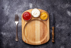Food background with mustard, ketchup, mayonnaise, fork and knif Royalty Free Stock Photography