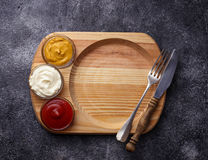 Food background with mustard, ketchup, mayonnaise, fork and knif Royalty Free Stock Images