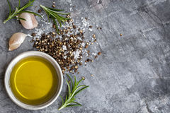Food Background Olive Oil Salt Peppercorns Rosemary and Garlic o. Food background with olive oil, peppercorns, sea salt, rosemary, and garlic cloves, over dark royalty free stock image