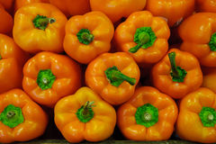 Food background - orange bell peppers with green stalks forming a symmetrical display. Healthy organic orange bell papers with contrast green stalk at the Farmer Stock Photo