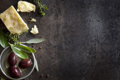Food Background. With parmesan cheese, fresh herbs and olives, over dark slate.  Lots of copy space Royalty Free Stock Image