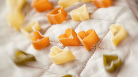 Food background. Pasta hearts on the kitchen textiles. Selective focus. Close-up colorful macaroni. Food background. Pasta hearts on the kitchen textiles Royalty Free Stock Photography