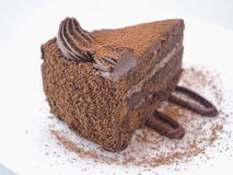 Food background. Piece of chocolate cake isolated on white. Slice of fresh brownie arranged on white plate.  Close-up image. Selective focus on the front Royalty Free Stock Photography