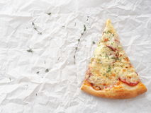 Food background.  Piece of freshly made pepperoni pizza upon baking parchment. Homemade pizza with thyme. Copy space for your text Stock Photo
