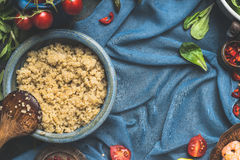 Food background for Quinoa recipes and cooking. Cooked quinoa with wooden spoon and vegetables ingredients on dark blue background Royalty Free Stock Images
