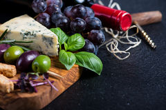 Food background,rustic board with cheese herbs and wine Royalty Free Stock Photos