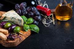 Food background,rustic board with cheese herbs and wine Royalty Free Stock Photography