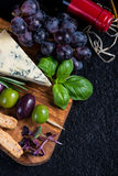 Food background,rustic board with cheese herbs and wine Royalty Free Stock Image
