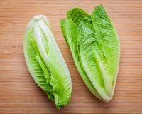 Food background and salad concept with fresh cos lettuce flat l. Ay on bamboo cutting board background stock image