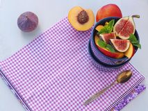 Food background. Summer fruits upon purple napkin and in a bowl with fresh mint leaves. Healthy eating concept. stock images