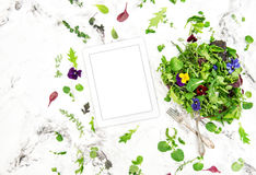Food background tablet salad herbs flowers Digital recipe book. Food background tablet PC. Green salad with herbs and flowers. Healthy organic nutrition. Digital Stock Images