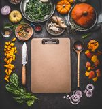 Food background for tasty winter and autumn dishes with pumpkin. Various cooking ingredients with spoon and knife around blank car. Dboard clipboard for menu or stock images