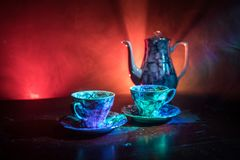 Food background tea and coffee theme. Old vintage ceramic tea or coffee pot with cups jug and sugar cup on dark background with li. Coffee or tea ceremony stock photography