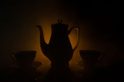 Food background tea and coffee theme. Old vintage ceramic tea or coffee pot with cups jug and sugar cup on dark background with li Stock Photos