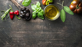 Food background with vegetables, herbs and condiment. Greek black olives, fresh basil, sage, rosemary, tomato, peppers. Oil on dark rustic wooden background Royalty Free Stock Photos