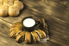 Food. Baking of confectionery. Fresh baked bakery roll with poppy seeds and sesame seeds with a cup of milk for breakfast on stock image