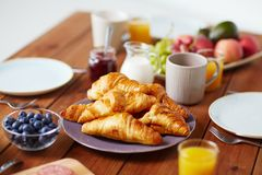 Plate of croissants on wooden table at breakfast Stock Photos