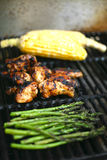 Food on the barbecue - chicken, sweetcorn and asparagus royalty free stock photography