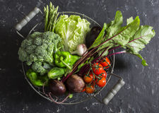 Food basket with fresh garden vegetables - beets, broccoli, eggplant, asparagus, peppers, tomatoes, cabbage on a dark table. Top view Stock Image