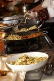 Food being prepared at a wedding function. This is an image of food being created during a function. Very shallow depth of field, with focus on the center pan royalty free stock images