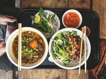 Food at the Ben Thanh food market in Ho Chi Minh City in Vietnam. Delicious Bun bo nam bo and beef stew with chilli sauce, carrot vinegar sauce and mungo stalks stock image