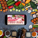 Big set of vegetables, spices and smartphone on a black background. Food blog concept. Big set of vegetables, spices and smartphone on a black background Stock Photography