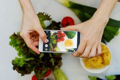 Food blogger concept. Hands with the phone close-up pictures of food. Top view Royalty Free Stock Image