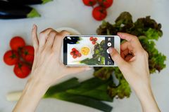 Food blogger concept. Hands with the phone close-up pictures of food. Top view Royalty Free Stock Images