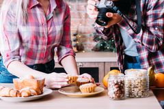 Food blogger dessert photo fresh muffins pastries. Food blogger. Dessert assortment. Woman and men taking photo of fresh muffins. Homemade pastries, jars with stock photos