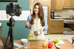 Food blogger recording a video. Pretty young Latin female food blogger working on a new video and explaining how to cook a dish royalty free stock photo