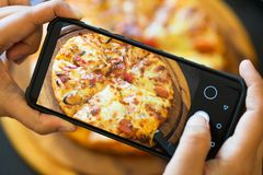 Food blogger taking picture of cooked pizza. Woman& x27;s hands with smartphone takes picture of fresh baked hot selfmade pizza. Photography blogging workshop stock images
