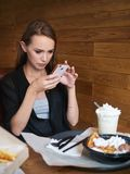 Food blogger woman sitting at the table with french fries, vienna waffles, cream drink in coffee shop. Happy caucasian female. Doing fast food photos on stock photo