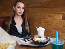 Food blogger woman sitting at the table with french fries, vienna waffles, cream drink in coffee shop. Happy caucasian female with. Fast food dishes in cafe royalty free stock photography