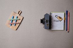 Food blogging, blog and blogger or social media concept: symbol hashtag, notepad and a retro photo camera on a grey background. Flat lay royalty free stock photos