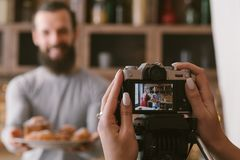 Food blogging business couple lifestyle pastries. Food blogging business. Couple lifestyle. Woman shooting men with fresh homemade pastries assortment royalty free stock photo