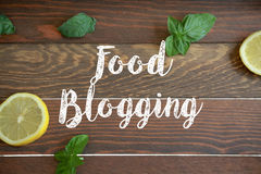 Food blogging sign. On wooden background with lemon and mint stock photography