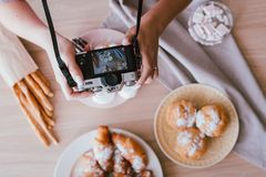 Food blogging woman hobby homemade cakes pastries. Food blogging hobby. Sweet homemade bakery assortment. Woman shooting fresh cakes and pastries from above royalty free stock photos
