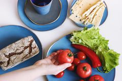 Food in blue designer dishes on light background. Women`s hand holding tomato. royalty free stock image