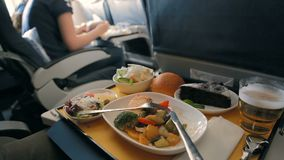 Tray of food on the airplane. Food on board. Dinner on an airplane. Food served on business class airplane stock video