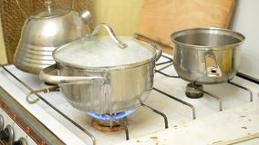 Food boiling over in saucepan. Food boiling over in stainless steel saucepan with transparent glass top on old dirty white gas cooker. There's a tea kettle and stock footage