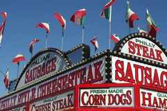 Food Booth at a County Fair. Red and white sign and flags on a food booth at a county fair royalty free stock photography