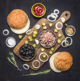 Food burger with tuna Food burger with tuna, herbs, cucumbers, olives, onions and sauce on a cutting board on wooden rustic backgr Royalty Free Stock Photography