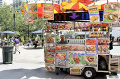 Food Cart in New York City. Vendor looks out from his varied menu Hot Dog stand on 34th and Broadway near Herald Square in Manhattan Stock Photo